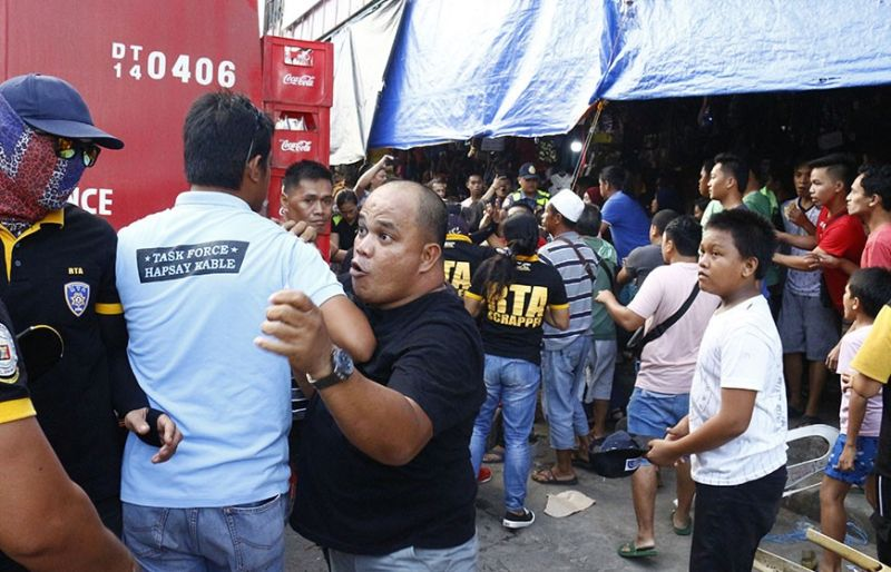 CAGAYAN DE ORO. The leader of the clearing team (in white shirt) from the Roads and Traffic Administration (RTA) is trying to pacify the ambulant vendors who allegedly went violent during the road clearing operation at Cogon public market, Wednesday, December 18. (Contributed photo)