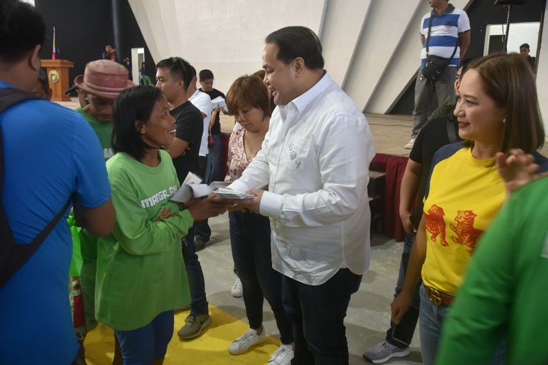 "PAMPANGA. One of the 1,505 scavenger beneficiaries happily receives her gifts from Governor Dennis ""Delta"" Pineda on Friday, December 20, during the ""Mangalakal: Kayantabe King Kalinisan at Kaayusan Assembly"" at the Bren Z. Guiao Convention Center in the City of San Fernando. (Jun Jaso)"
