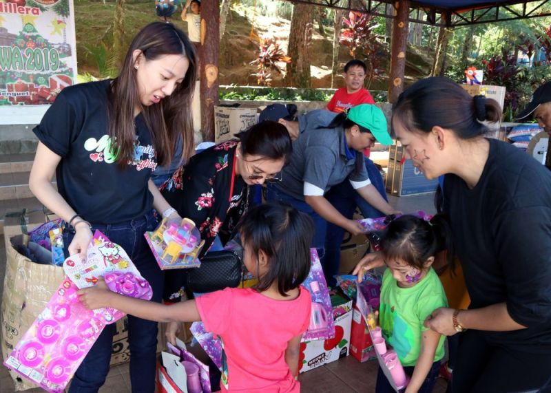 BAGUIO. Carmelyn Dickson, wife of Police Regional Office-Cordillera Regional Director Brigadier General Israel Dickson, and daughter Paola distributes gifts and goodies to children of police officers during the Christmas celebration at Camp Bado Dangwa last week. (Redjie Melvic Cawis)