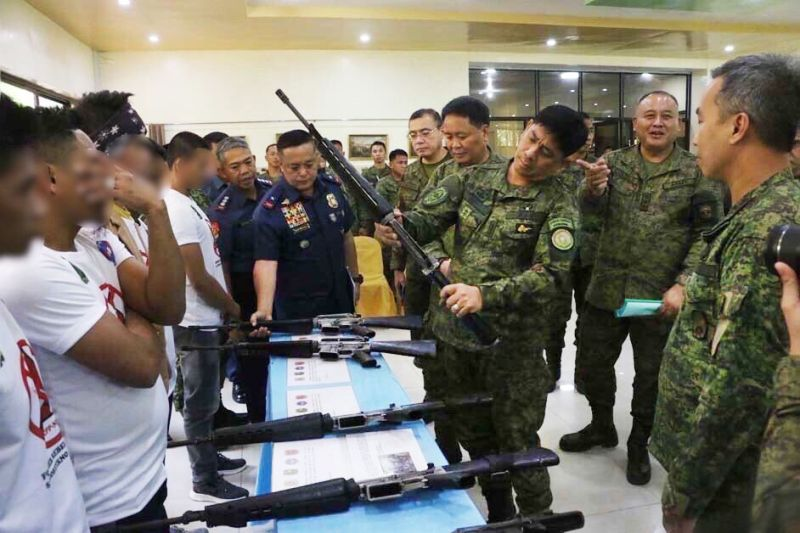 FORT MAGSAYSAY. Former rebels who used to be members of the Komiteng Larangang Gerilya Sierra Madre present to Northern Luzon Command Commander Lieutenant General Ramiro Manuel A. Rey (middle) the high-powered firearms that was discovered by security forces, from the information they gave, in a firearms cache in barangay Villa, Maria Aurora town in Aurora. (Contributed by 7th Infantry Division)