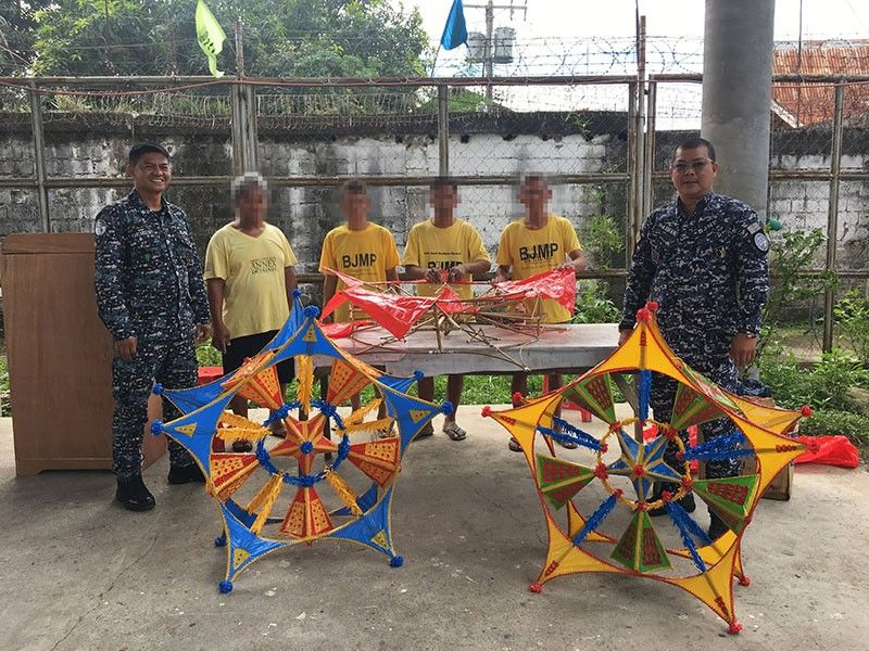 Persons Deprived of Liberty (PDLs) pose with Davao City Jail Annex warden Ian Glenn Ocmen and Bureau of Jail Management and Penology (BJMP) unit welfare and development chief Edwin Lim Naidas while making Christmas lanterns. (Roberto A. Gumba Jr.)