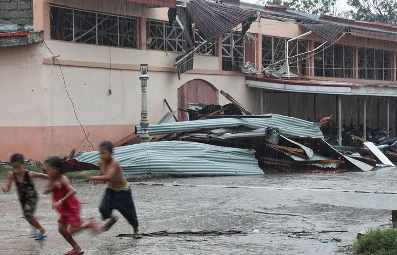 URSULA'S FURY. Rain soaks children running in front of the damaged covered court that had been used as an evacuation center in Daanbantayan town, Cebu.  Typhoon Ursula destroyed some 6,000 houses and damaged 12,000 other houses in northern Cebu. More photos on Page 7. (Contributed photo/Capitol PIO)