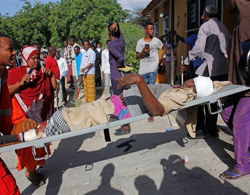 SOMALIA. Medical personnel carry a civilian who was wounded in a suicide car bomb attack at a check point in Mogadishu, Somalia, Saturday, December 28, 2019. A police officer said a car bomb detonated at a security checkpoint during the morning rush hour in Somalia's capital. (AP)