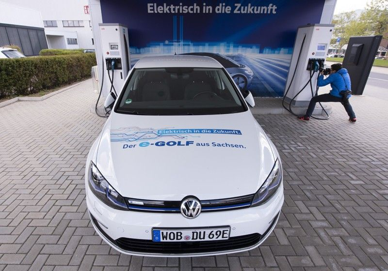 GERMANY. In this Tuesday, May 14, 2019 file photo an e-Golf car stands at the charging station during a press tour of the plant of the German manufacturer Volkswagen AG (VW) in Zwickau, Germany. Automaker Volkswagen is raising the bar for its plunge into battery powered cars, saying it will reach its goal of 1 million e-autos per year two years earlier than planned. The slogans read:
