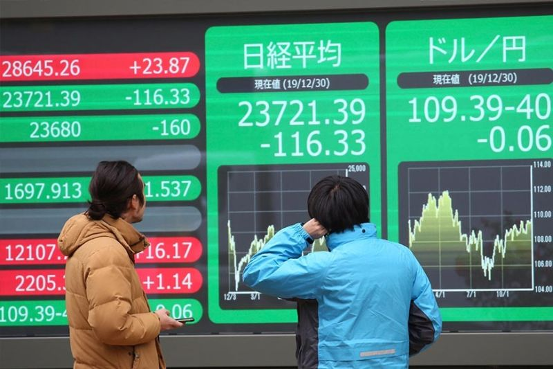 WAIT AND SEE. People look at an electronic stock board of a securities firm in Tokyo, Monday, Dec. 30, 2019. Asian shares were mostly lower Monday as investors awaited updates on the signing of a trade deal between the United States and China and kept a wary eye on North Korea. (AP photo)
