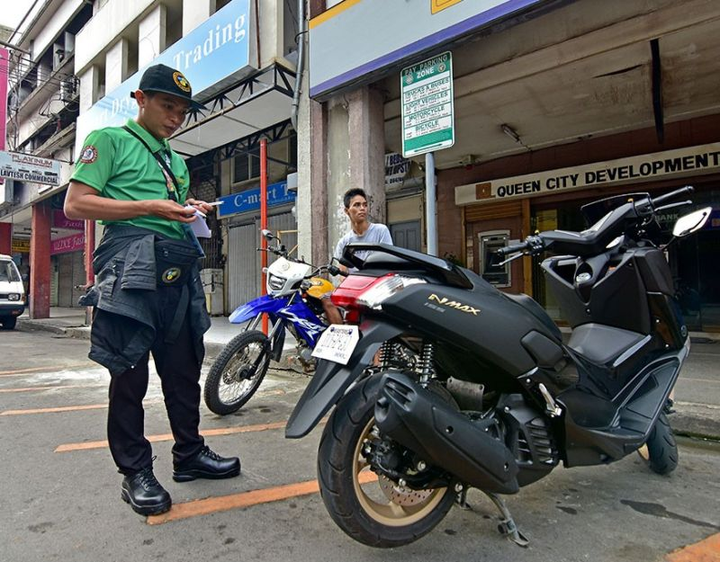 DAVAO. A Davao City Transport and Traffic Management Office staff notes the plate number and time of parking of a motorcycle as the CTTMO implements the pay parking scheme on several streets in the city wherein motorcycles will pay P5 and P20 for light vehicles for the first two hours. (Macky Lim)