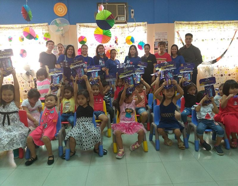 "SAN FERNANDO. Day care kids are all smiles as they show their gifts from SM Supermalls during the recent ""KriSMiles"" Christmas gathering. (Contributed photo)"