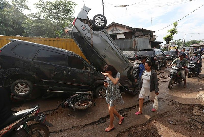 INDONESIA. Residents walk near the wreckage of cars that were swept away by flood in Bekasi, West Java, Indonesia, Friday, January 3, 2020. Severe flooding in greater Jakarta has killed scores of people and displaced tens of thousands others, the country's disaster management agency said. (AP Photo)