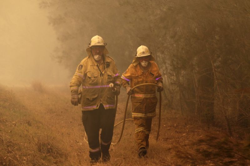 AUSTRALIA. Firefighters drag their water hose after putting out a spot fire near Moruya, Australia, Saturday, January 4, 2020. Australia's Prime Minister Scott Morrison called up about 3,000 reservists as the threat of wildfires escalated Saturday in at least three states with two more deaths, and strong winds and high temperatures were forecast to bring flames to populated areas including the suburbs of Sydney. (AP)