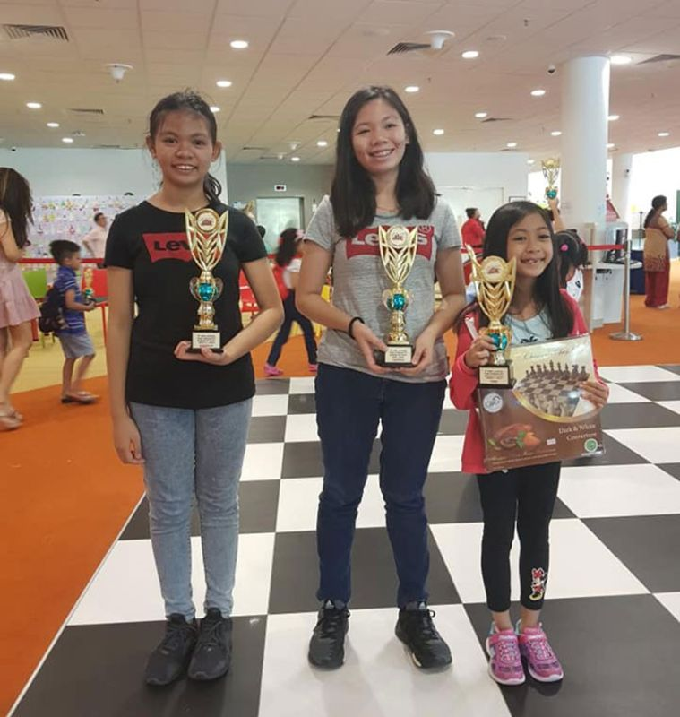 SINGAPORE. Chess sisters. From left, 11-year-old Jeanne Reese Marie, 15-year-old Joannah Love Marie, and seven-year-old Jasmine Reign Marie Olay of Kidapawan City pose with their trophies at the close of the CASPL Christmas Rapid Chess Challenge 2019 held at the Singapore Sports Hub Library in Singapore recently. (Edgar Reggie Olay)