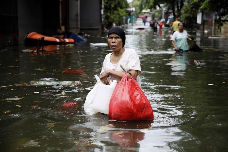 INDONESIA. A woman wades flood water in Jakarta, Indonesia, Saturday, January 4, 2020. Monsoon rains and rising rivers submerged parts of greater Jakarta and caused landslides in neighboring regions which buried a number of people. (AP)