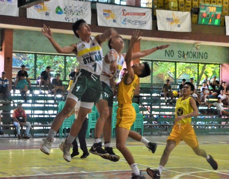 CSAV Titans' Joshua Dayon (1) blocks the shot of SNHS Golden Stags guard Christian Joshua Fuentrespina (7) during their opening match in the NBTC-Bacolod Leg last Saturday. (Jerome S. Galunan Jr. Photo)