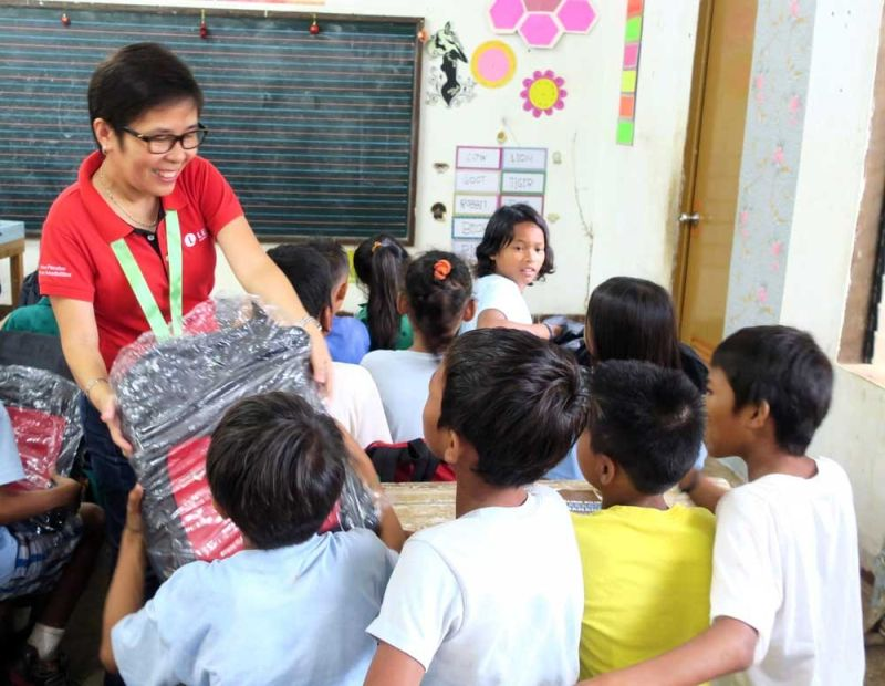 HELPING STUDENTS. Lear Corp. human resources director Amabel Abella distributes kits containing basic school supplies, backpacks, umbrellas and tumblers to the students of Sabang Elementary School in Olango Island, Lapu-Lapu City. (CONTRIBUTED FOTO )