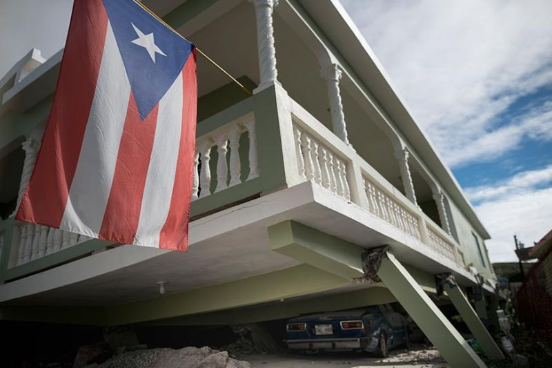 PUERTO RICO. A Puerto Rican flag hangs from the porch of a home that collapsed on top of parked cars after an earthquake hit Guanica, Puerto Rico, Monday, January 6, 2020. A 5.8 magnitude quake hit Puerto Rico before dawn Monday, unleashing small landslides, causing power outages and severely cracking some homes. There were no immediate reports of casualties. (AP)