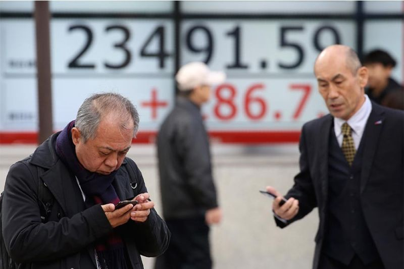 REBOUND. People walk by an electronic stock board of a securities firm in Tokyo, Tuesday, Jan. 7, 2020. Shares are climbing in Asia following modest gains on Wall Street despite caution over rising tensions between the United States and Iran. (AP photo)