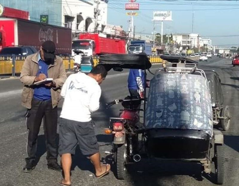 PAMPANGA. A traffic enforcer in the City of San Fernando apprehend a driver in line with the enforcement of tricycle ban on major thoroughfares. (CPOSCO photo)