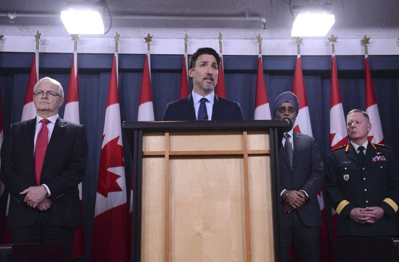 CANADA. Prime Minister Justin Trudeau holds a press conference in Ottawa on Wednesday, January 8, 2020, flanked by Transport Minister Marc Garneau (left), Defence Minister Harjit Sajjan and General Jonathan Vance. (AP)