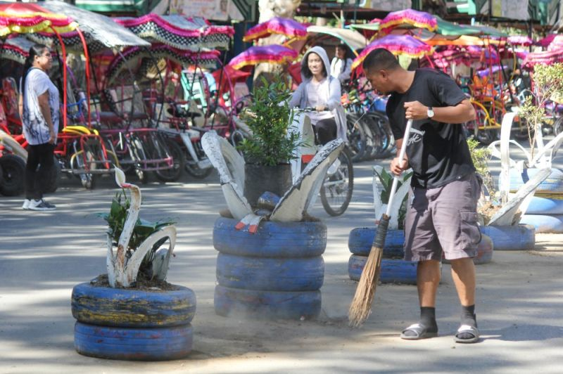 BAGUION CITY. Tenants at the biking area in Burnham Park conduct early morning clean-up to keep the area neat, while waiting for customers. (Photo by Jean Nicole Cortes)