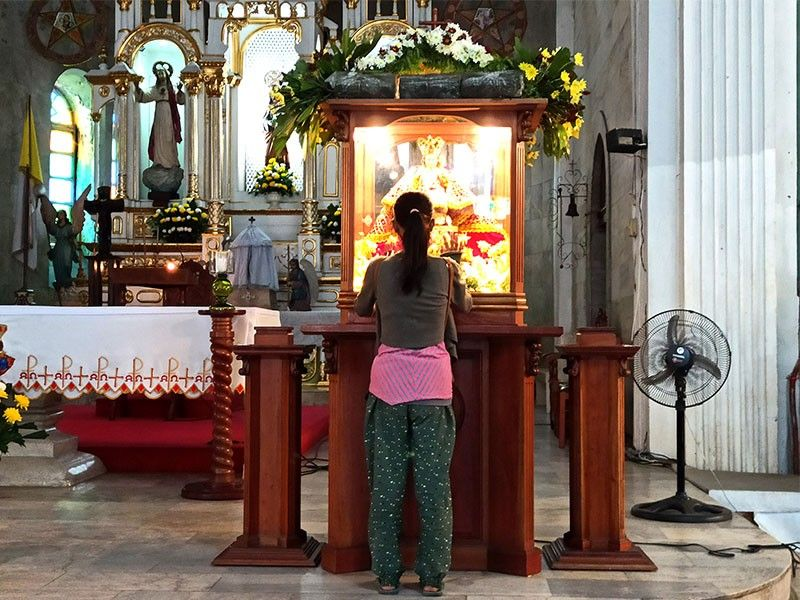 A devotee of Señor Santo Niño prays inside the San Jose Parish Pacer in Iloilo City, home of Señor Santo Niño de Cebu in Iloilo, on Friday, January 10, 2020. (Photo by Leo Solinap)