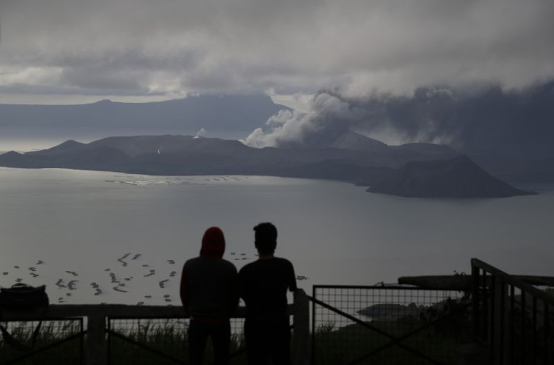 TAGAYTAY. Men watch from Tagaytay, Cavite province, as Taal Volcano continues to spew ash on Tuesday, January 14, 2020. Thousands of people fled the area through heavy ash as experts warned that the eruption could get worse and plans were being made to evacuate more. (AP)