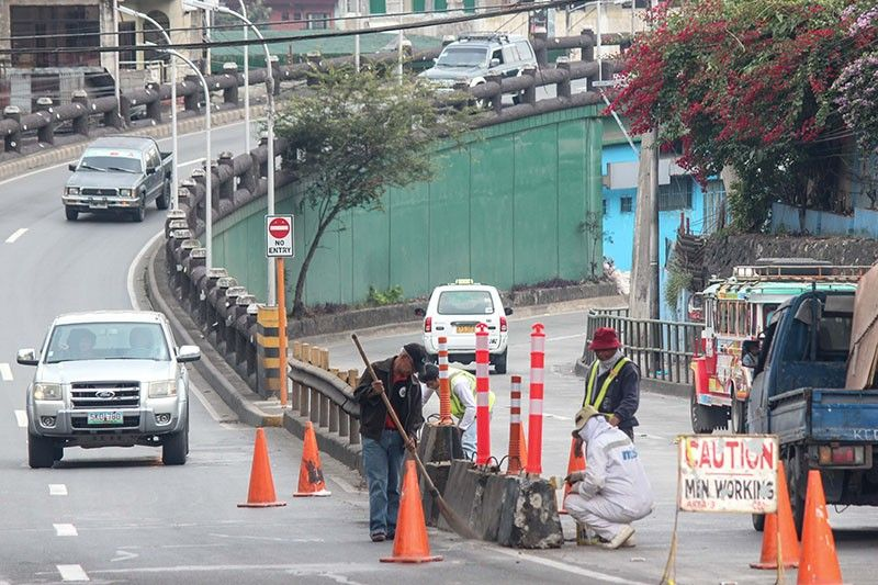 ROAD SAFETY. Government workers in Baguio City clean the road safety traffic barriers along Magsaysay Avenue. (Jean Nicole Cortes)