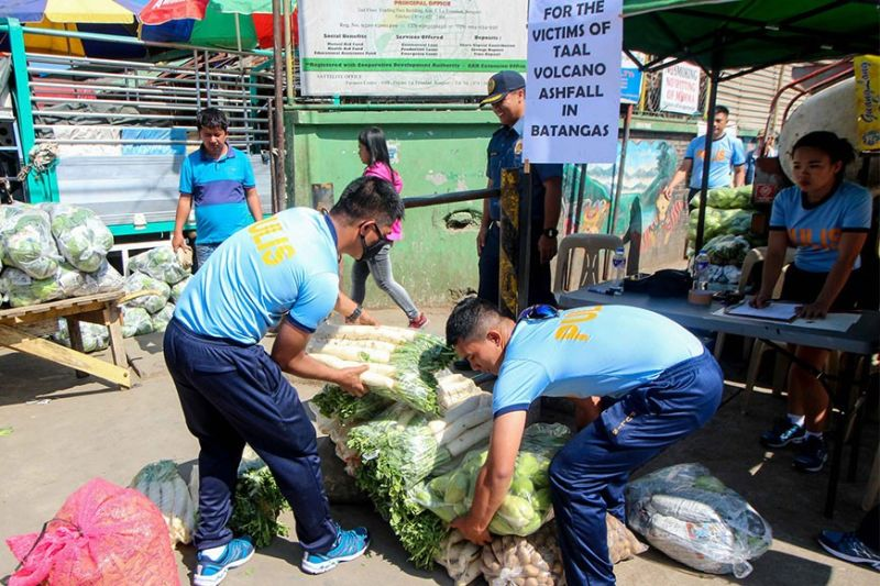 "BENGUET. Police officers assist in the collection of vegetables given by farmers and concerned citizens at the La Trinidad Vegetable Trading Post on Thursday, January 16, which marks the second day of the ""Gulay para sa mga kapatid natin sa Batangas"" which started on January 15. Some 3,000 kilos of vegetable were delivered in Lipa City on its first day while the second batch will be donated in Ibaan, Batangas. (Photo by Jean Nicole Cortes)"