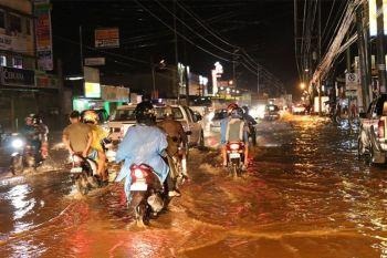 DAVAO CITY. Tungod sa kusog nga pag-ulan nga nasinati niadtong Huwebes, Enero 16 sa gabii, tagbaw sa pagpugong sa ilang balanse ang pipila ka mga drayber sa motorsiklo sa dihang gilatas ang gibaha nga dapit sa Daang Maharlika Highway, siyudad sa Davao. (Hulagway ni Mark Perandos)
