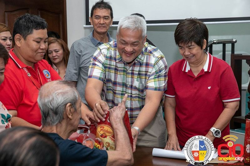 "PAMPANGA. Angeles City Mayor Carmelo ""Pogi"" Lazatin, Jr. distributes the social pension and ham packages of some indigent senior citizens from various barangays in the city at Legislative Building, City Hall Compound. Assisting him during the distribution were Gender and Development Officer Mina Cabiles, City Social Welfare and Development Office personnel led by Edna Duaso, and Office for Senior Citizens Affairs personnel. (Contributed photo)"