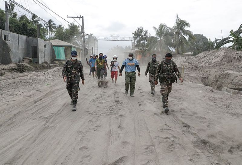 BATANGAS. Police and military men walk along a road covered in volcanic ash at a village beside Taal volcano where residents have evacuated to safer ground in Agoncillo, Batangas province on Saturday, January 18, 2020. (AP)