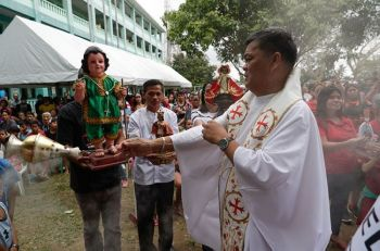 CAVITE. Catholic priest Armando Timojo (right) blesses images of the baby Jesus after a mass to celebrate its feast day at an evacuation center near Taal volcano in Tagaytay, Cavite on Sunday, January 19, 2020. (AP)