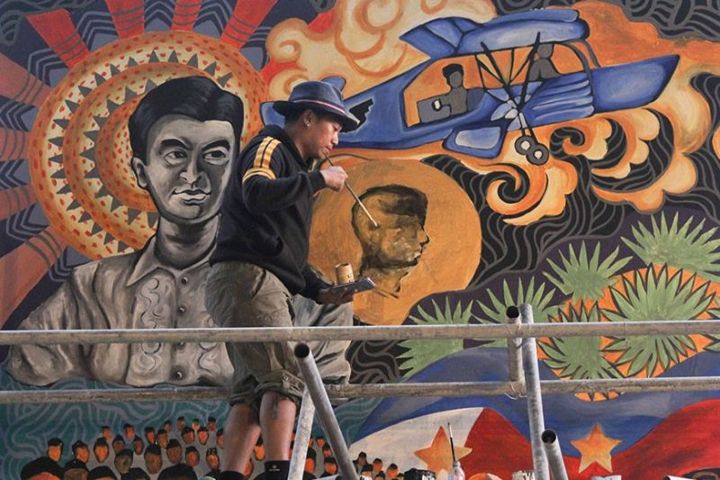 BAGUIO. Artist Angelo Aurelio puts on finishing touches on the mural painting depicting the late president Ramon Magsaysay at the Magsaysay Elementary School in New Lucban, Baguio City. (Jean Nicole Cortes)