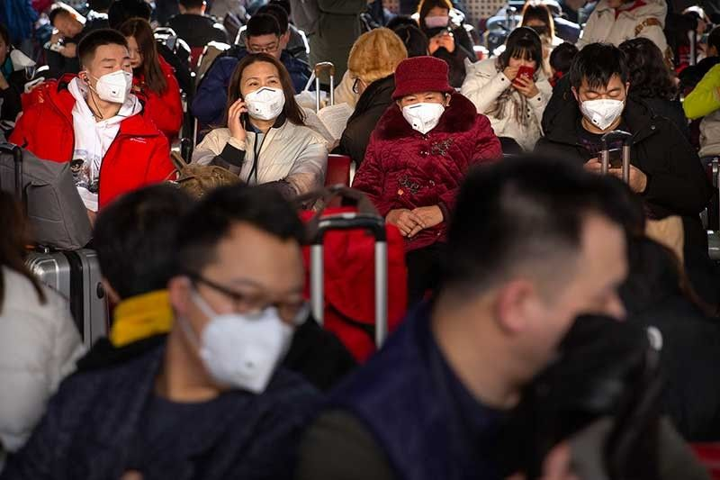 CHINA. Travelers wear face masks as they sit in a waiting room at the Beijing West Railway Station in Beijing, Tuesday, January 21, 2020. A fourth person has died in an outbreak of a new coronavirus in China, authorities said Tuesday, as more places stepped up medical screening of travelers from the country as it enters its busiest travel period. (AP Photo)