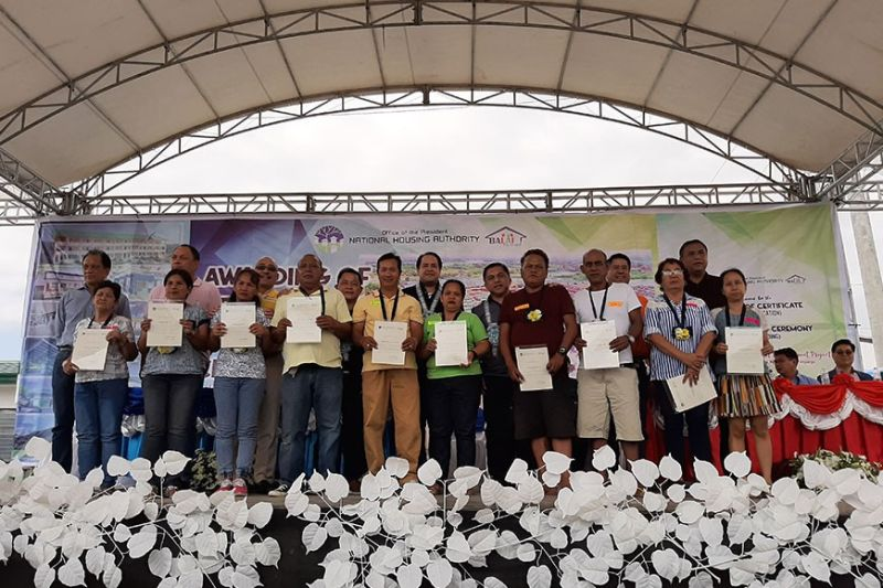 PAMPANGA. Recipients of housing units at Golden Residences Resettlement Center formally received their land titles from National Housing Authority General Manager Marcelino Escalada Jr., Rep. Juan Pablo Bondoc, Governor Dennis Pineda, Masantol Mayor Danilo Guintu, Vice Mayor Boboy Lacap, Pampanga Mayors' League President Edgar Flores, and Board Members Pol Balingit and Nelson Calara. (Princess Clea Arcellaz)