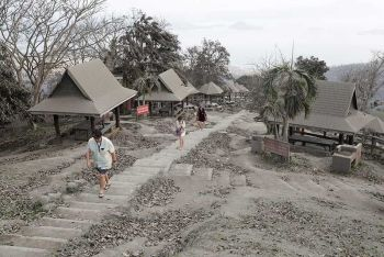 CAVITE. People walk along a park covered in volcanic ash at a town near Taal Volcano in Tagaytay, Cavite province on Sunday, January 19, 2020. Officials said Sunday the government will no longer allow villagers to return to their homes on Taa Volcano Island. (AP Photo)