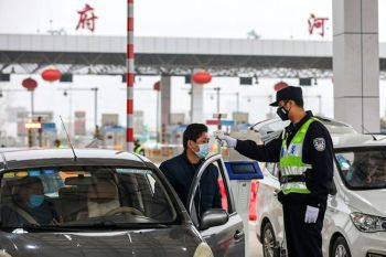 CHINA. A policeman uses a digital thermometer to take a driver's temperature at a checkpoint at a highway toll gate in Wuhan in central China's Hubei Province, Thursday, January 23, 2020. (AP)