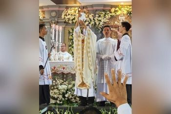 """TRADITIONAL CHANGE. Fr. Pacifico Nohara Jr. raises the image of the Sto. Niño during the traditional """"Hubo"""" Mass at the Basilica Minore del Sto. Niño de Cebu in Cebu City on Friday, Jan. 24, 2020. During the Mass, the vestments of the Sto. Niño image were changed. (SunStar photo / Arni Aclao)"""