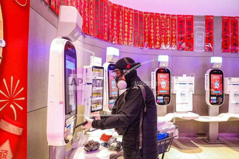 CHINA. A shopper wearing goggles, a face mask and gloves uses a self checkout machine at a supermarket in Wuhan in central China's Hubei province, Saturday, Jan. 25, 2020. (Chinatopix via AP)