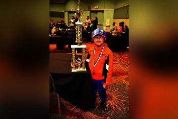 Little Scott Escalera with his giant chess trophy (Supplied Photo)