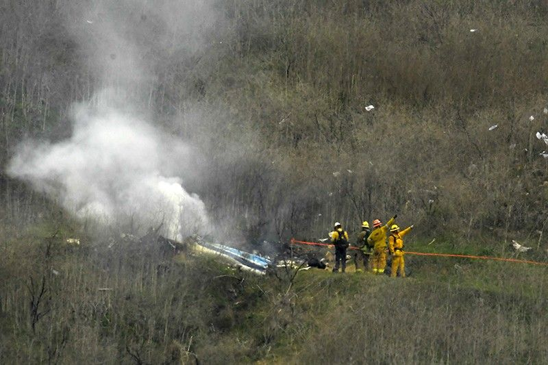 Firefighters work the scene of a helicopter crash where former NBA star Kobe Bryant died, Sunday, Jan. 26, 2020, in Calabasas, Calif. (AP Photo)