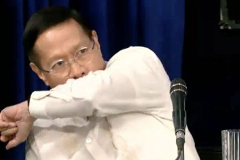 MANILA. Health Secretary Francisco Duque III demonstrates the proper coughing etiquette for those who don't have tissue to cover their mouths with. (Photo grabbed from RTVM video)