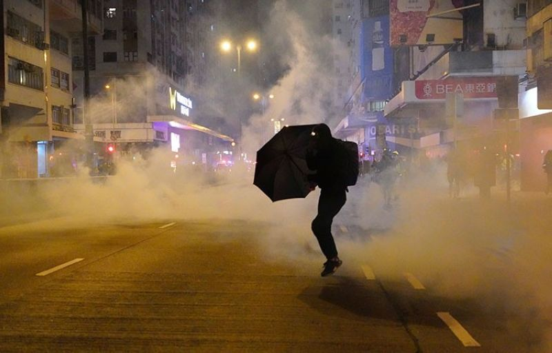 HONG KONG. In this January 1, 2020, file photo, a protester holds an umbrella as police fire tear gas during a demonstration in Hong Kong. (AP)