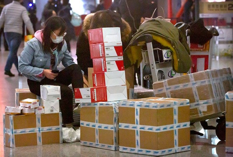 CHINA. A traveler sits near boxes of face masks and respirators at the Beijing Capital International Airport in Beijing, Thursday, January 30, 2020. (AP)