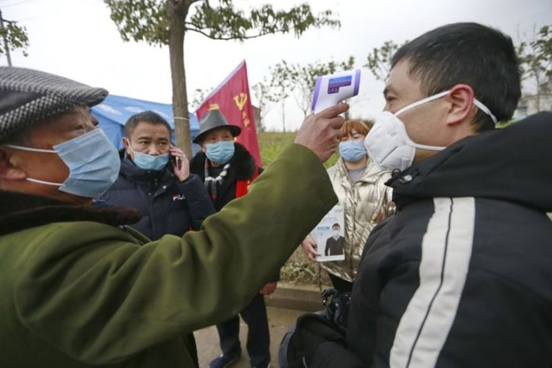 In this Saturday, Feb. 1, 2020, photo, a government worker takes the temperature of a passer-by at a checkpoint in Suining in southwestern China's Sichuan Province. (Chinatopix via AP)