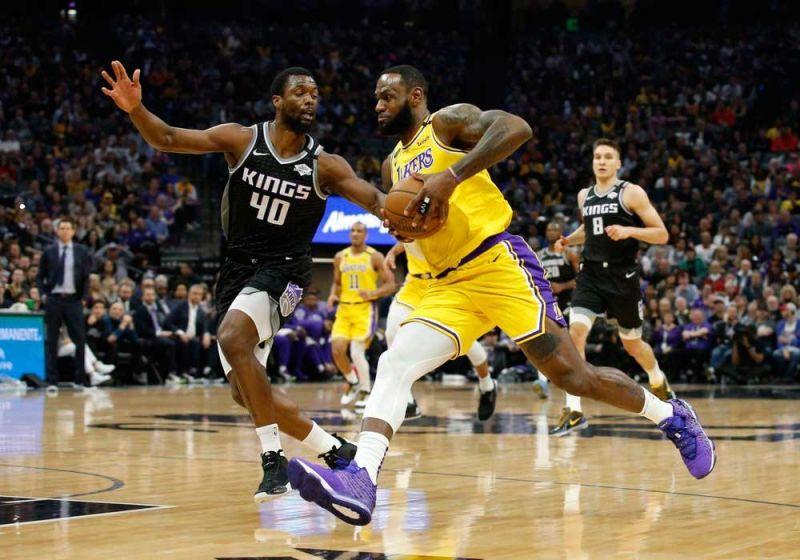 MIHUNAT: Si LeBron James (tuo) sa Los Angeles Lakers milusot batok ni Harrison Barnes sa Sacramento Kings niining aktoha atol sa ilang duwa kagahapon sa NBA. (AP)