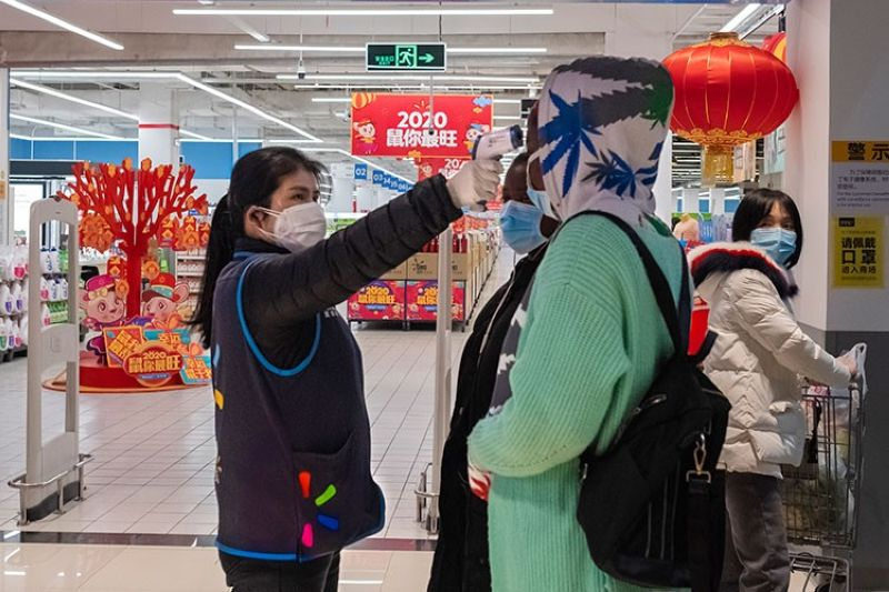 CHINA. In this January 27, 2020 file photo, a worker takes the temperature of a customer at the entrance of a Walmart store in Wuhan in central China's Hubei Province. (AP/Arek Rataj)