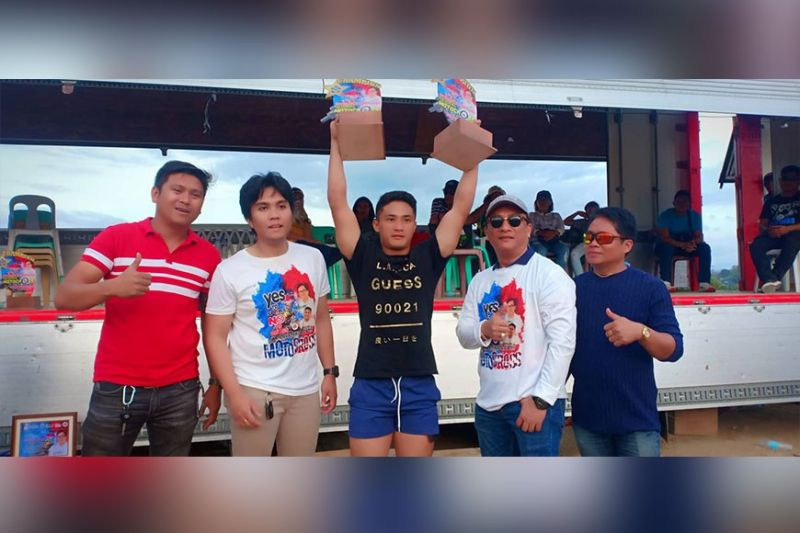 CAGAYAN DE ORO. Terrence Napat, 19, of M'lang, North Cotabato, steals the spotlight from the legendary Glenn Aguilar of Manila in the recent National Motocross Open in Tagoloan, Misamis Oriental. With him during the awards rites are Tagoloan Mayor Enan Sabio, Mohon village chair and event coordinator Jeyson Sabio and host barangay captain of Natumolan Rafael Vidal. (Lynde Salgados)