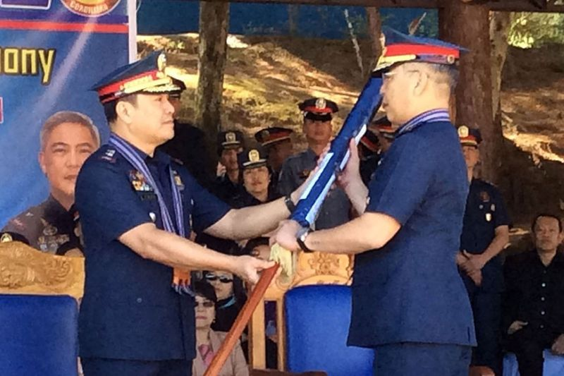 BENGUET. Police Major General Gilberto Cruz hands over the Police Regional Office – Cordillera command flag to newly installed regional director R'win Pagkalinawan during Tuesday's turnover ceremony at Camp Bado Dangwa in La Trinidad, Benguet. (Photo by Jonathan Llanes)