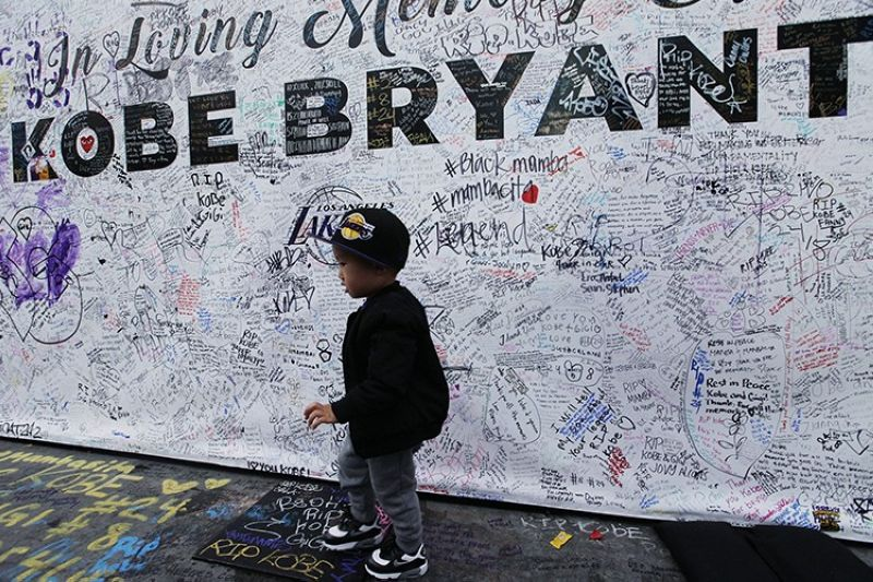 A boy walks by a standing board with messages for the late Kobe Bryant at a memorial for Bryant in front of Staples Center in Los Angeles Sunday, Feb. 2, 2020. Bryant, the 18-time NBA All-Star who won five championships and became one of the greatest basketball players of his generation during a 20-year career with the Lakers, died in a helicopter crash Sunday, Jan. 26. (AP)