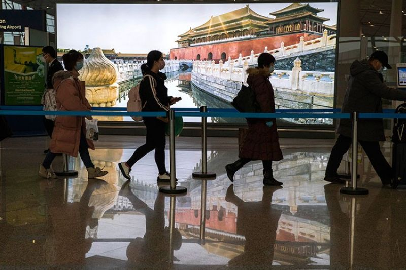 CHINA. Passengers wearing mask for protection arrive at the airport in Beijing on Sunday, February 9, 2020. (AP)