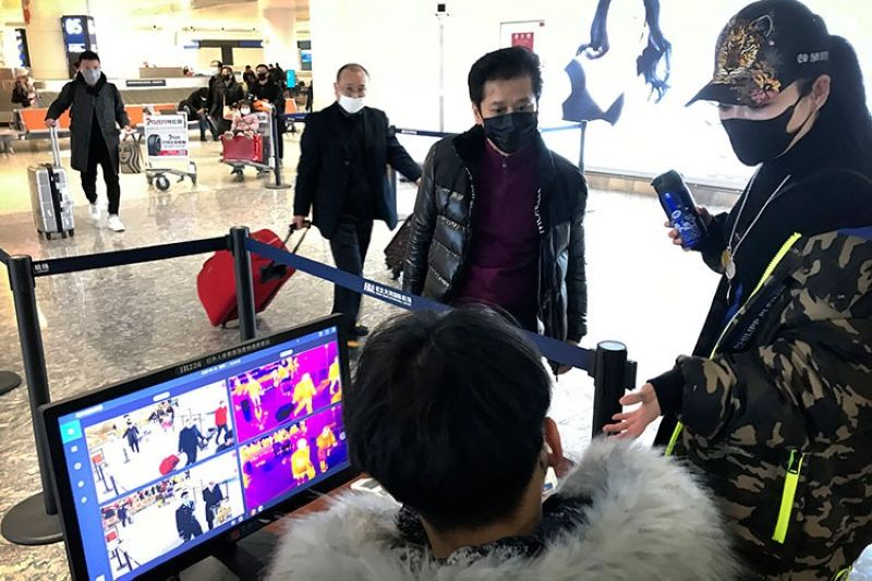 CHINA. In this January 21, 2020, file photo, travelers pass through a health screening checkpoint at Wuhan Tianhe International Airport in Wuhan in southern China's Hubei province. (AP)